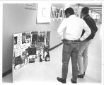Two men viewing a collage in the hallway of the natural science office, circa 1970