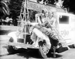 Two women with microphone sitting on car, circa 1920-1935