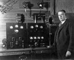 Douglas Perham standing beside radio equipment, 1922