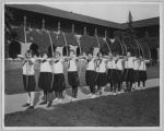 Archery students pose with bows and arrows in the San Jose quad, circa 1925