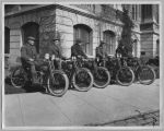 Five men sitting on Harley-Davidson motorcycles in front of courthouse, San Jose, California,...