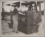 Woman in Overalls Running Machinery, circa 1915